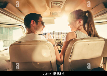 Young couple sitting in cockpit of propeller airplane - Stock Photo