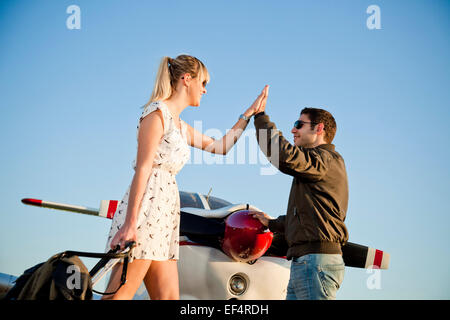 Couple giving each other high-five in front of private airplane - Stock Photo