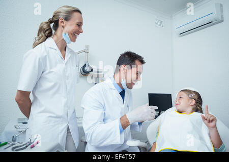 Male dentist  and assistant talking to girl - Stock Photo