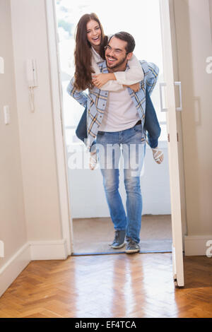 Young man giving girlfriend a piggyback ride - Stock Photo