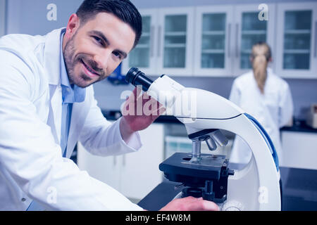 Science student working with microscope in the lab - Stock Photo