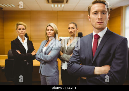 Serious lawyer standing with arms crossed - Stock Photo