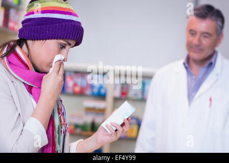 Sick woman with scarf and colorful hat holding a box of drug - Stock Photo