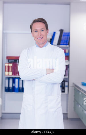 Portrait of a smiling biochemist standing with arms crossed - Stock Photo