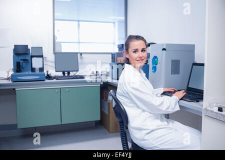 Smiling young biochemist using laptop at her desk - Stock Photo