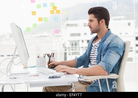 Concentrated designer using computer and digitizer - Stock Photo