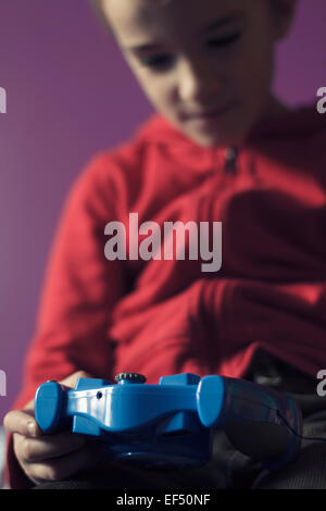 Young boy indoors playing a video game. - Stock Photo