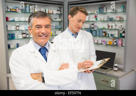 Senior pharmacist smiling at camera - Stock Photo