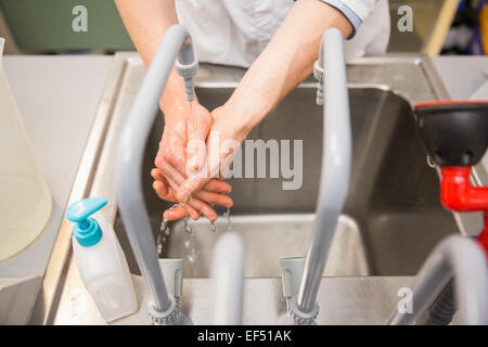 Pharmacist washing his hands at sink - Stock Photo