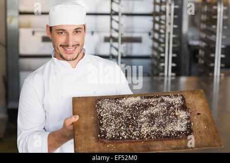 Baker showing freshly baked brownie - Stock Photo