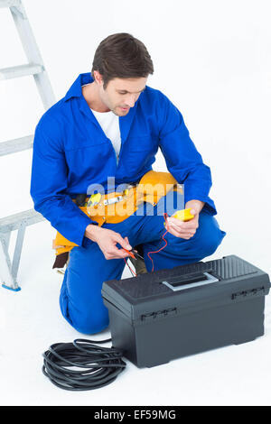 Electrician using multimeter over white background - Stock Photo