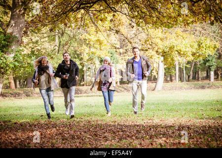 Group of friends running through autumn park - Stock Photo