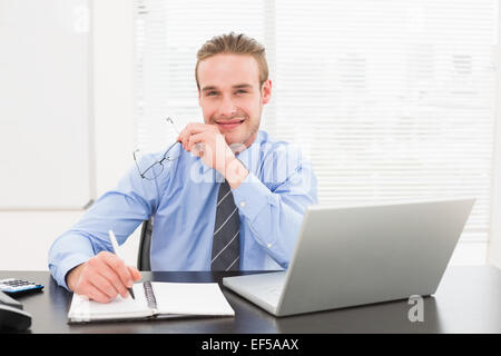 Smiling businessman taking notes on notebook - Stock Photo