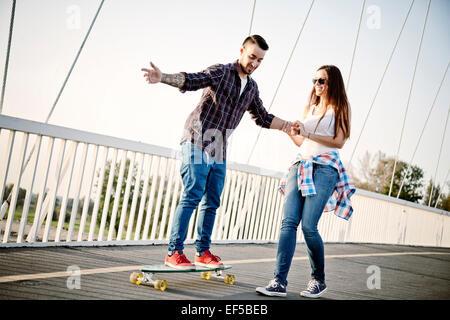 Young man balancing on skateboard, woman assisting - Stock Photo