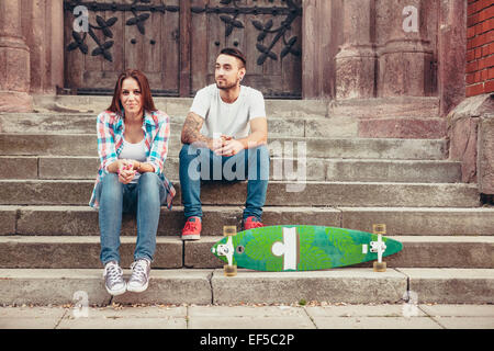 Young couple with skateboard taking a break on staircase - Stock Photo