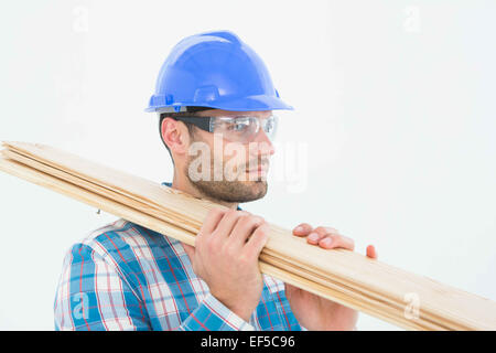 Confident carpenter carrying wooden planks - Stock Photo