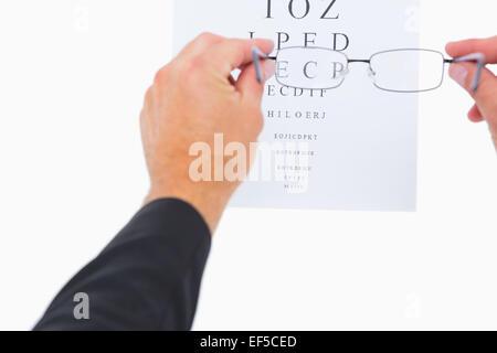 Man holding eyeglasses over paper - Stock Photo