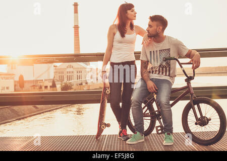 Young couple with skateboard and BMX bicycle resting on bridge - Stock Photo