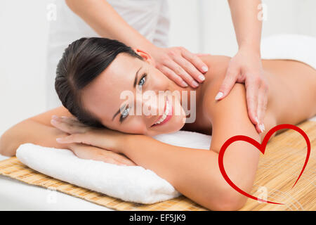 Composite image of beautiful brunette enjoying a shoulder massage smiling at camera - Stock Photo