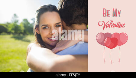 Composite image of loving and happy woman embracing man at park - Stock Photo