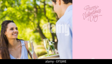 Composite image of couple with champagne flutes sitting at an outdoor café - Stock Photo