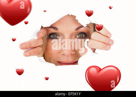 Composite image of woman looking through torn paper