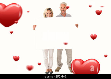 Composite image of happy couple holding large poster - Stock Photo
