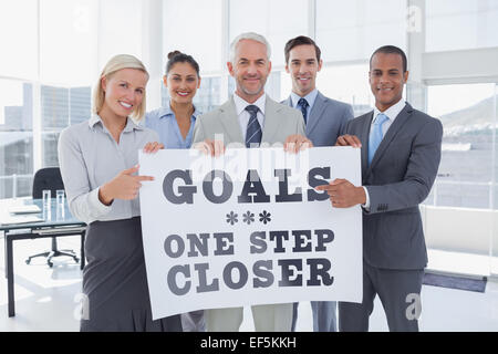 Composite image of business team holding large blank poster and pointing to it - Stock Photo