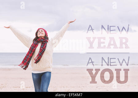 Composite image of woman in warm clothing stretching arms on beach - Stock Photo