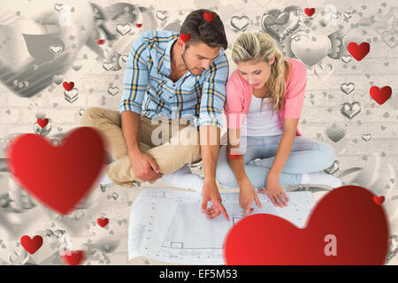 Composite image of attractive young couple sitting looking at blueprint - Stock Photo