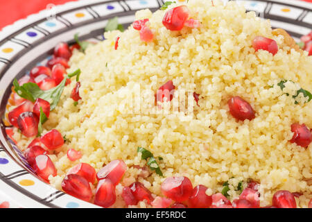 couscous with pomegranate seeds, walnuts and parsley - Stock Photo