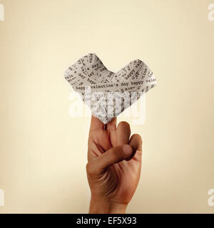 the hand of a young man holding a heart made-up with paper strips with the text happy valentines day, with a retro - Stock Photo