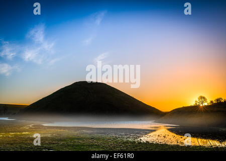 The mist recedes as the sun rises over the historic monument of Silbury Hill near Avebury in Wiltshire. - Stock Photo