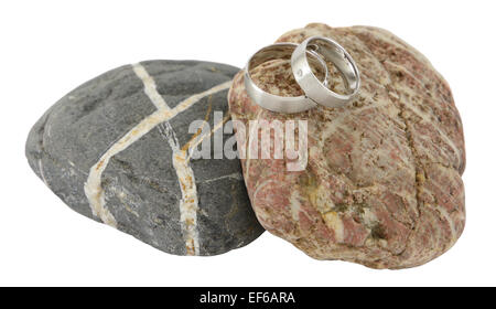 Two wedding rings on stone isolated on white. - Stock Photo