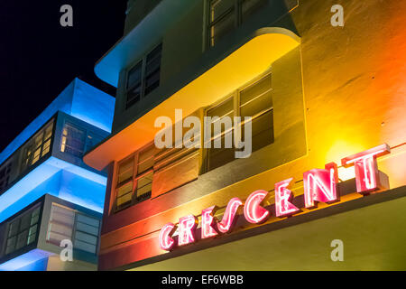 Crescent Hotel's Art Deco yellow facade illuminated at night by red neon sign along Deco Drive on Miami Beach, Florida - Stock Photo