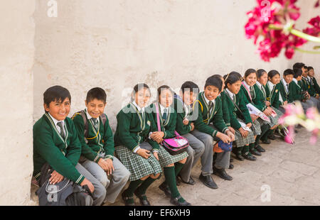 Local happy Peruvian schoolchildren in school uniform sitting on a bench having fun enjoying visiting Santa Catalina - Stock Photo