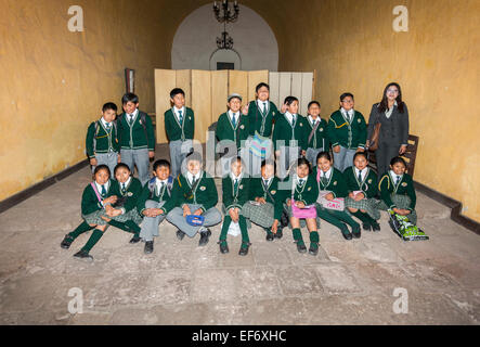 Class of local Peruvian schoolchildren in school uniform posing for a class group picture enjoying visiting Santa - Stock Photo