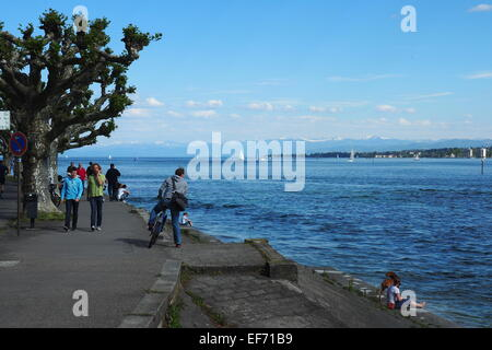Walkers and a cyclist on the shore of Lake Konstanz with the Alps in the background. - Stock Photo
