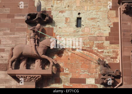 Red sandstone statue of St George slaying a dragon, on the exterior wall of Basel Minster. - Stock Photo
