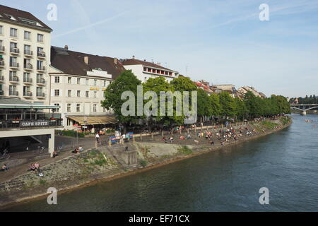 People sitting and sunbaking along the banks of the Rhine River in Basel. - Stock Photo