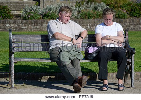 A sleeping couple sitting on a park bench in the sunshine - Stock Photo