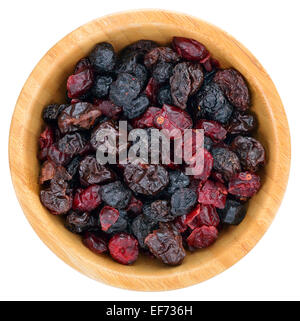 Dried mix berries fruits. Dried cranberries, raisins, sour cherries, blueberries in wooden bowl isolated on white - Stock Photo