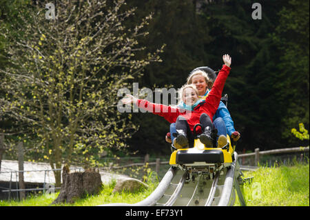 Young women on a summer toboggan run, Steinwasenpark in Oberried, Black Forest, Baden-Württemberg, Germany - Stock Photo