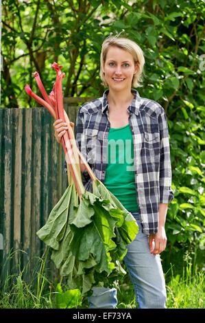 Woman with rhubarb - Stock Photo