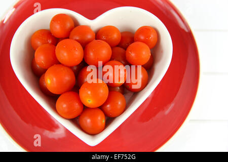 close up of bright red Cherry tomatoes in a heart shaped bowl on red plate on a white wood background. - Stock Photo