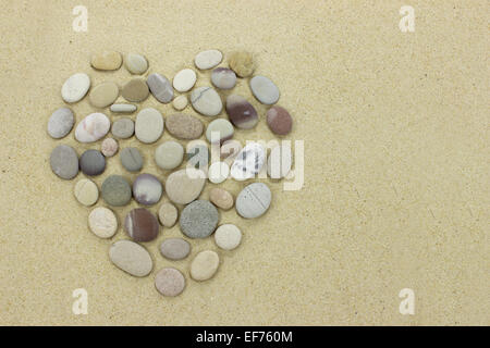heart made of beach stones on a sandy beach - Stock Photo