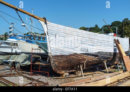 Old clinker built sailing boat being repaired in a boatyard on Exeter Quays,Exeter, Devon England - Stock Photo