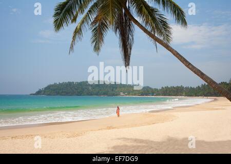 TOURIST WALKING ALONG SANDY BEACH WITH PALM TREE - Stock Photo