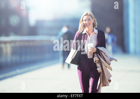 Businesswoman talking on cell phone on city sidewalk - Stock Photo