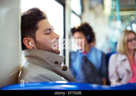 Businessman napping and listening to earbuds on train - Stock Photo